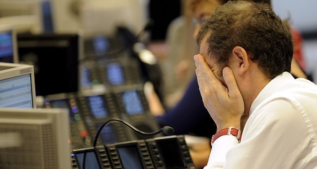 A trader covers his face with his hands at the stock exchange in Milan, Italy on Oct. 8, 2008. EPA Photo
