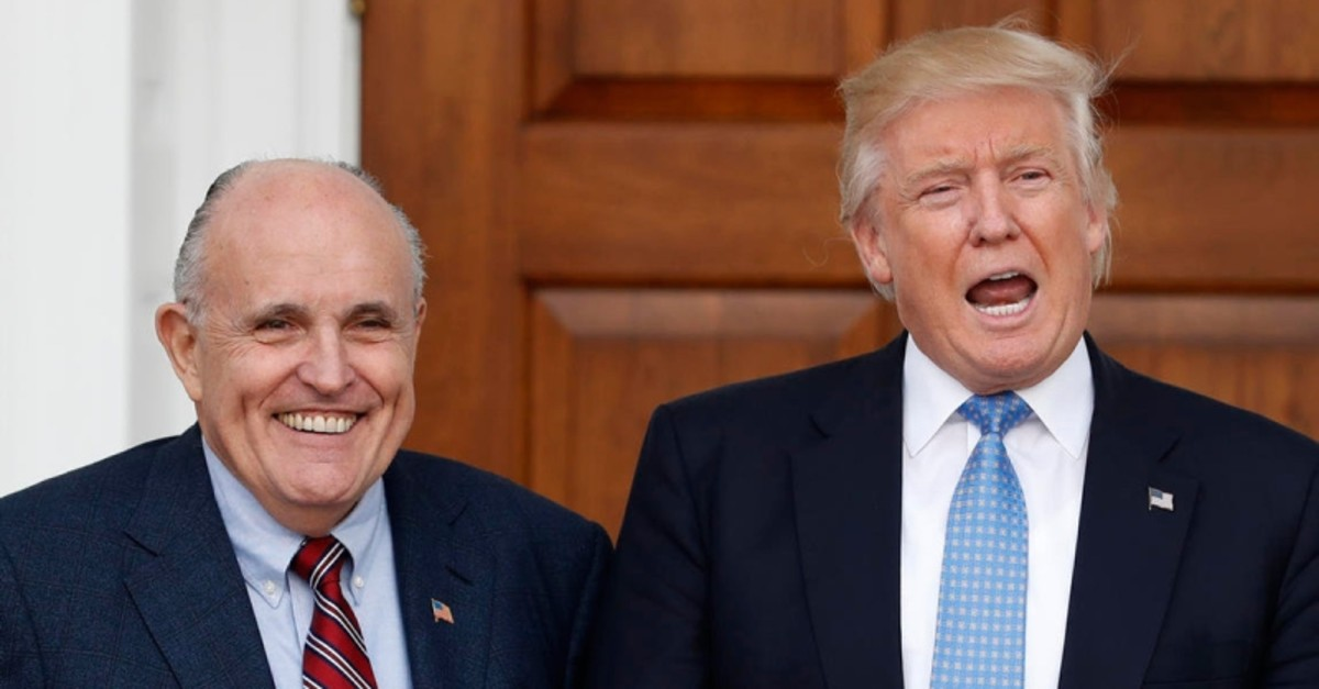 President-elect Donald Trump calls out to media as he and former New York Mayor Rudy Giuliani pose for photographs. (AP Photo)
