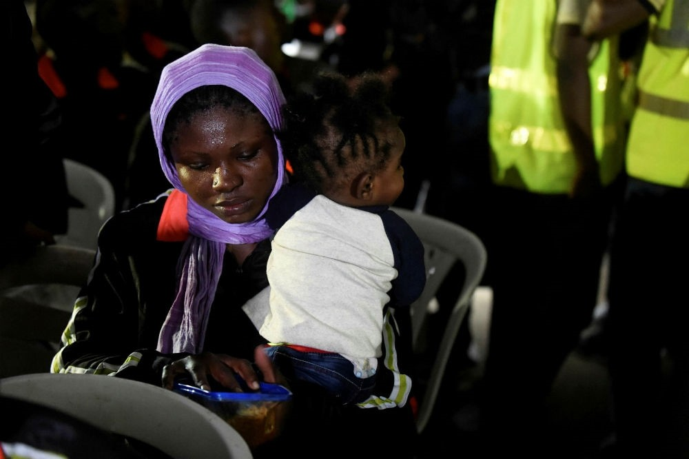 A returnee tries to feed a child after leaving a chartered aircraft that brought home 144 migrants from Libya, Dec. 5.
