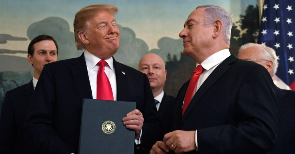 President Donald Trump smiles at Israeli Prime Minister Benjamin Netanyahu after signing a proclamation at the White House in Washington, March 25, 2019. (AP Photo)