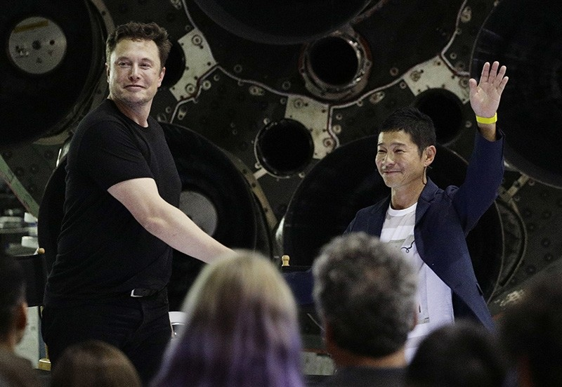 SpaceX founder and chief executive Elon Musk, left, shakes hands with Japanese billionaire Yusaku Maezawa, right, after announcing him as the first private passenger on a trip around the moon, Monday, Sept. 17, 2018, in Hawthorne, Calif. (AP Photo)