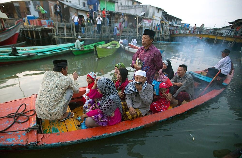 Indonesian Muslims leave their village by long boat to offer Eid al-Fitr prayers