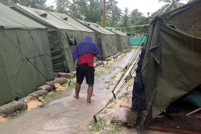 An undated handout file photo obtained from the Refugee Action Coalition on February 18, 2014 shows a man walking between tents at Australia's regional processing centre on Manus Island in Papua New Guinea. (AFP Photo)