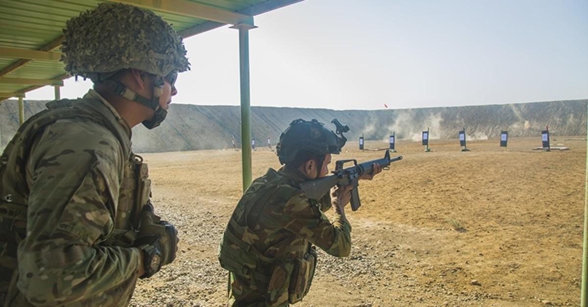 A British soldier supervises an Iraqi soldier assigned to the 71st Iraqi Army brigade as he fires an M16 rifle at a range at Camp Taji, Iraq, Oct. 11, 2015. (Public domain photo by U.S. Army Spc. William Marlow)