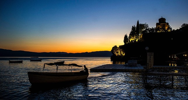 This file photo taken on August 14, 2016 shows a man piloting a boat in front of the St John Kaneo Church on the Lake Ohrid. (AFP Photo)