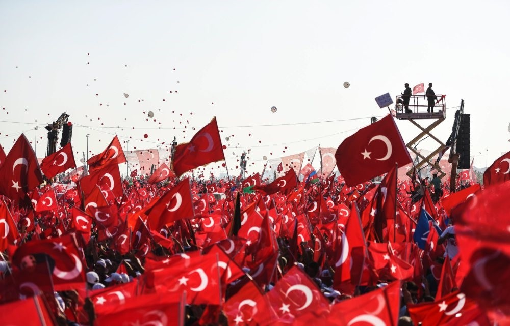 People wave Turkish flags as they stand in front of giant screens during a rally against the failed coup attempt by Gu00fclenist officers, Aug. 7, 2016.