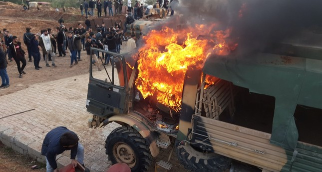 A military vehicle burns after protesters, provoked by PKK terrorists, stormed a Turkish military camp near Dohuk, Jan. 26, 2019.