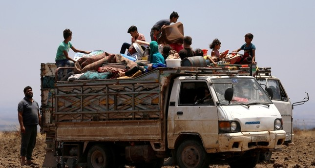 Internally displaced people from Deraa province sit on a truck loaded with belongings near the Israeli-occupied Golan Heights in Quneitra, Syria June 29, 2018. (REUTERS Photo)