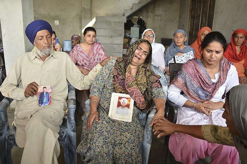 An Indian couple mourns holding portraits of their son, one of the 38 Indian workers whose bodies were found buried northwest of Mosul, in Bhoewal village in the northern Indian state of Punjab, March 20, 2018. (AP Photo)