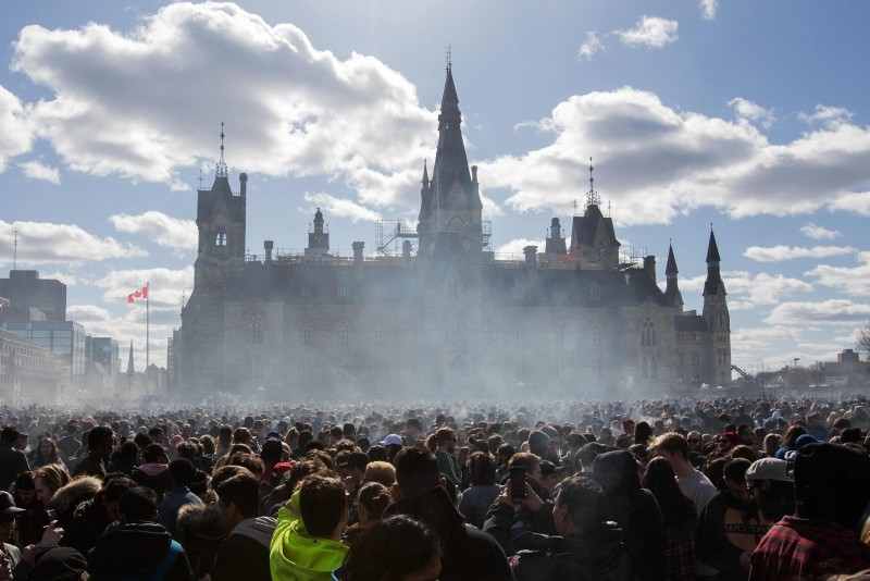 In this file photo taken on April 20, 2018 showing smoke lingers over Parliament Hill as people smoke marijuana during the annual 4/20 rally on Parliament Hill in Ottawa, Ontario. (AFP Photo)