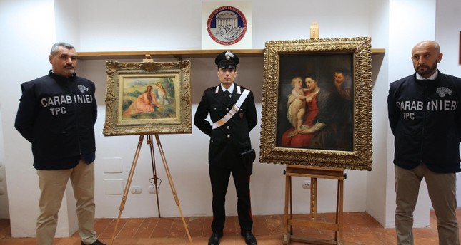 Italian carabinieri pose near the paintings 'Le fanciulle sul prato' by Renoir (L) and 'La Sacra Famiglia' by Rubens (R) during a press conference in Monza, Italy, 20 July 2018. (EPA Photo)