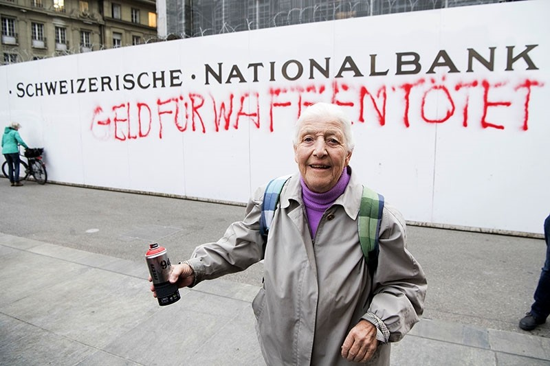 86-year-old activist Louise Schneider poses for media after spraying the words ,Money for Weapons Kills, (in German ,Geld Fuer Waffen toetet,) on a wall of the Swiss National Bank. (AP Photo)