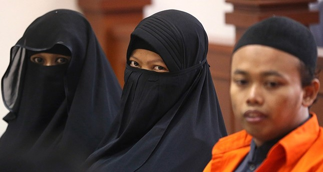 Terrorist Dian Yulia Novi, center, is flanked by her husband Nur Solihin, right, and her recruiter Tutin as they sit on the defendant's bench during their trial hearing at East Jakarta District Court in Jakarta, Indonesia