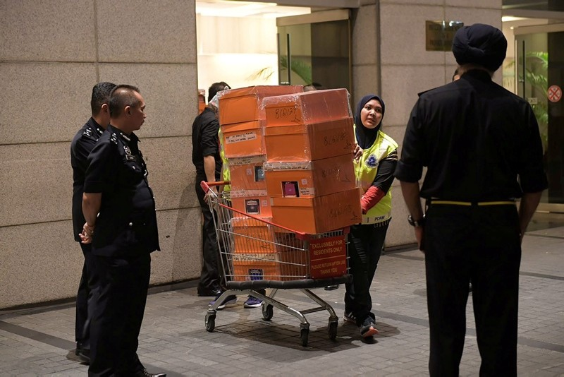 A Malaysian police officer pushes a trolley during a raid of three apartments in a condominum owned by former Malaysian prime minister Najib Razaku2019s family, in Kuala Lumpur, May 17, 2018, in this photo taken by The Straits Times. (REUTERS Photo)