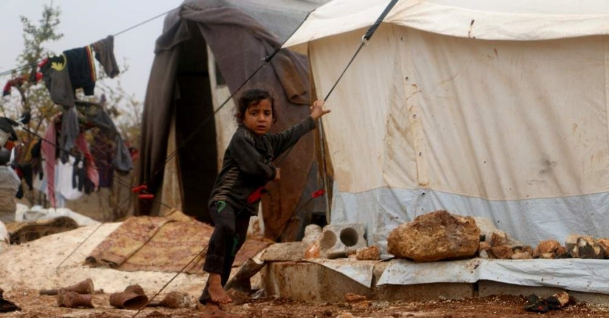 A child stands in front of a tent flooded with water in a camp near Idlib, Nov. 2, 2019. (AA Photo)
