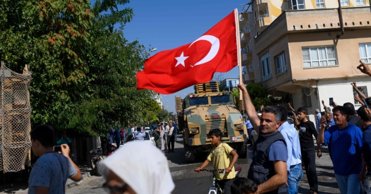 A man waves a Turkish flag as Turkey-backed Syrian opposition fighters enter Tel Abyad from the Turkish gate towards Syria in Aku00e7akale in u015eanlu0131ufa province on October 10, 2019. (AFP Photo)
