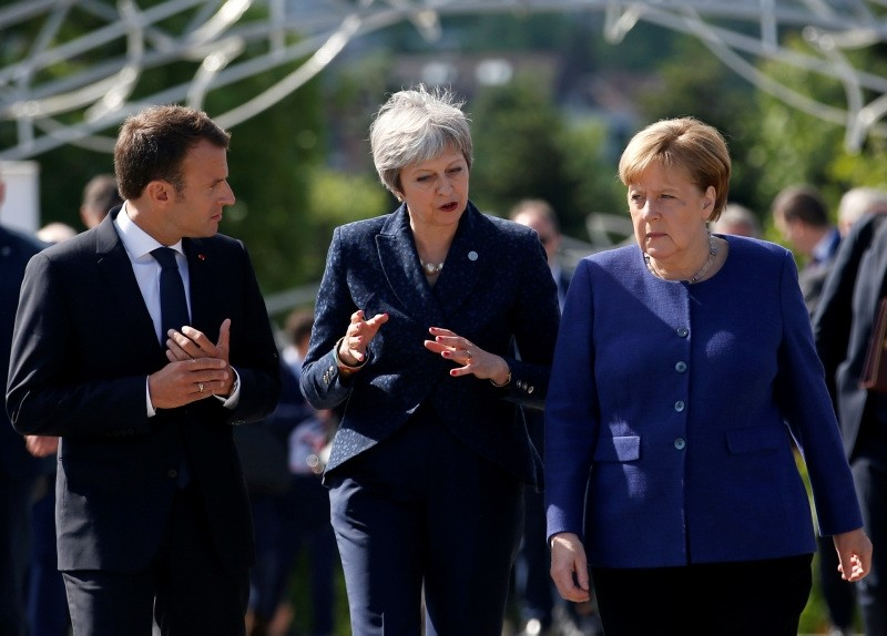German Chancellor Angela Merkel, right, speaks with French President Emmanuel Macron, left, and British Prime Minister Theresa May after meeting at a hotel on the sidelines of the EU-Western Balkans summit in Sofia, May 17, 2018. (AP Photo)