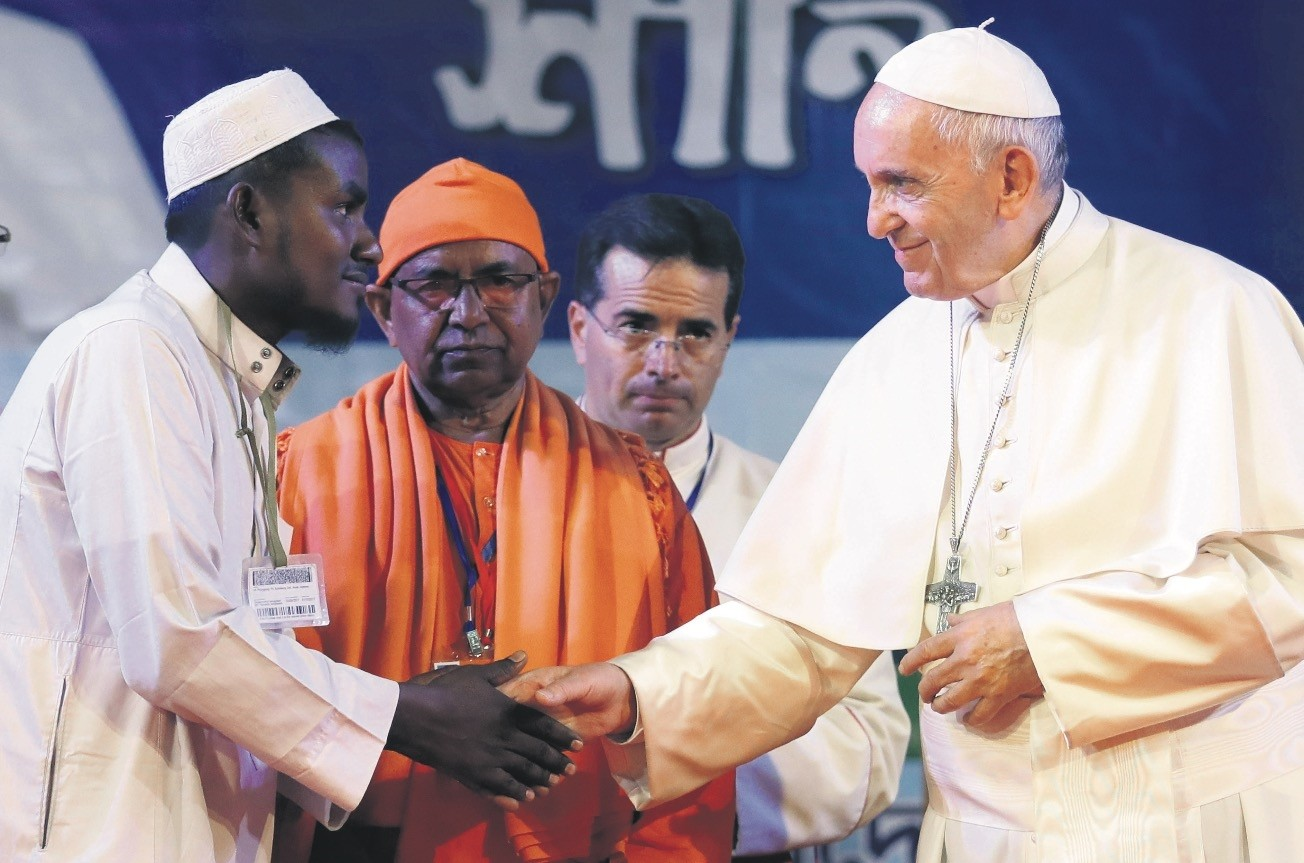 Pope Francis (R) shakes hands with a Rohingya Muslim refugee during an interfaith and ecumenical meeting for peace in the garden of the archbishop's residence, in Dhaka, Bangladesh.
