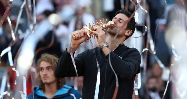 Serbia's Novak Djokovic celebrates with the trophy after winning the final against Greece's Stefanos Tsitsipas. (Reuters Photo)