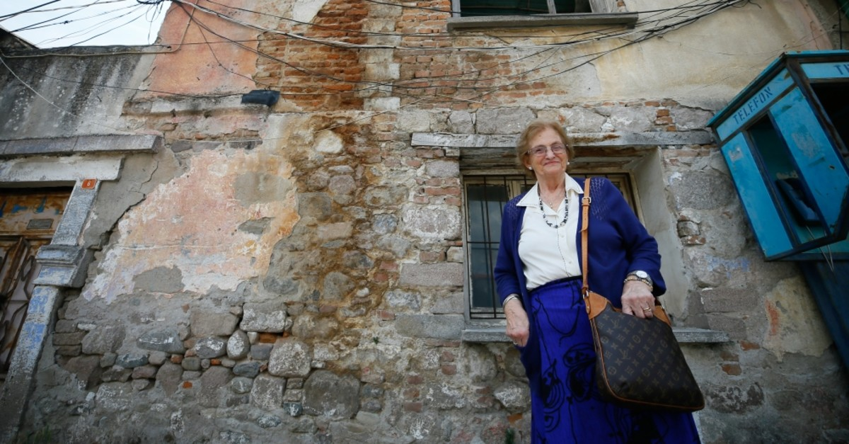 Rau015fel Kazes stands in front of an old house in her hometown Bergama, June 19, 2019.