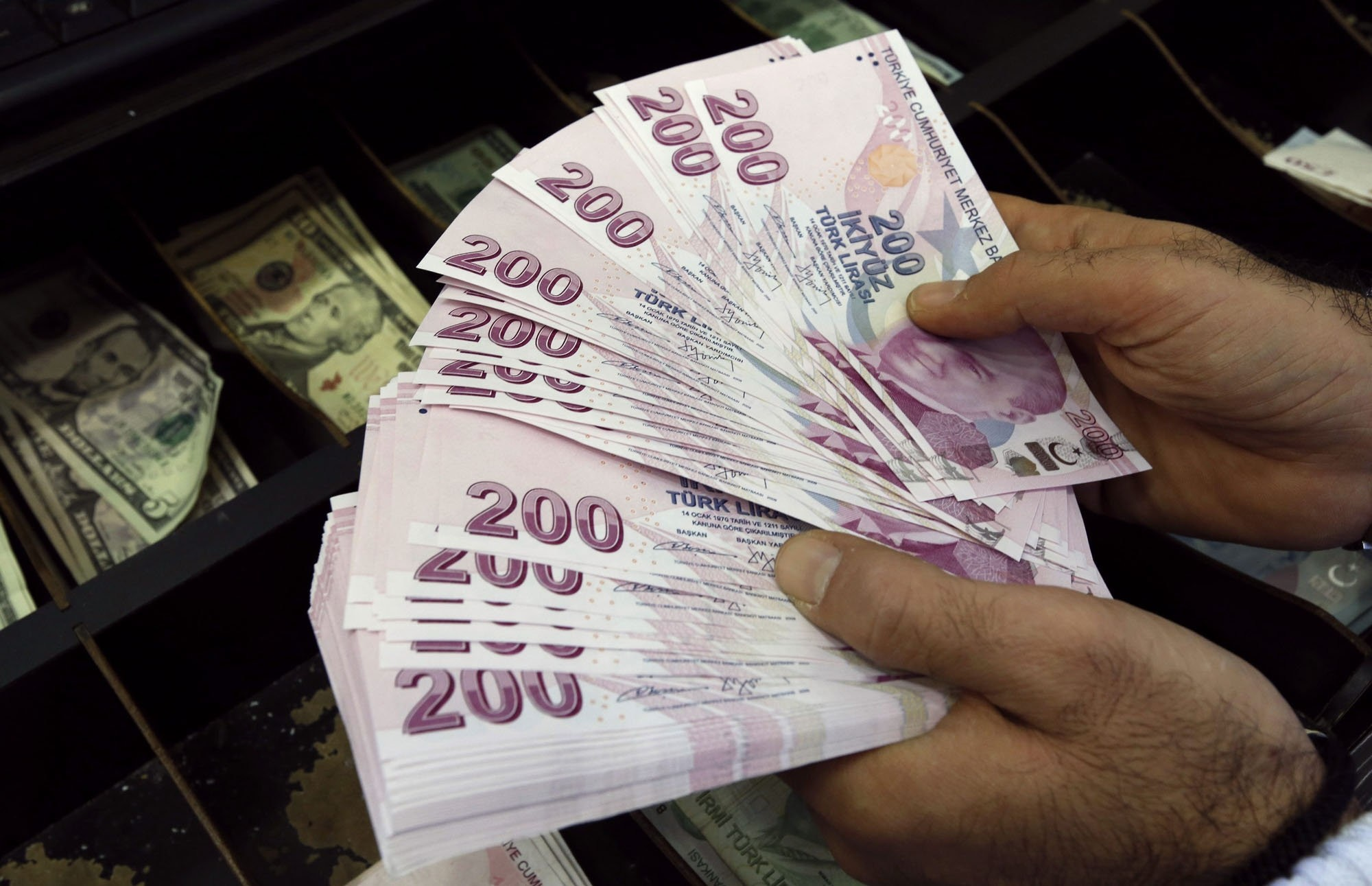 A money changer counts Turkish lira bills at a currency exchange office in Istanbul.