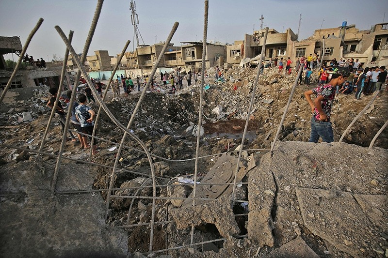 Iraqis inspect the aftermath of an explosion in Baghdad's Sadr City district on June 7, 2018. (AFP Photo)