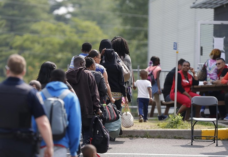 A group of asylum seekers wait to be processed after being escorted from their tent encampment to the Canada Border Services in Lacolle, Quebec (Reuters Photo)