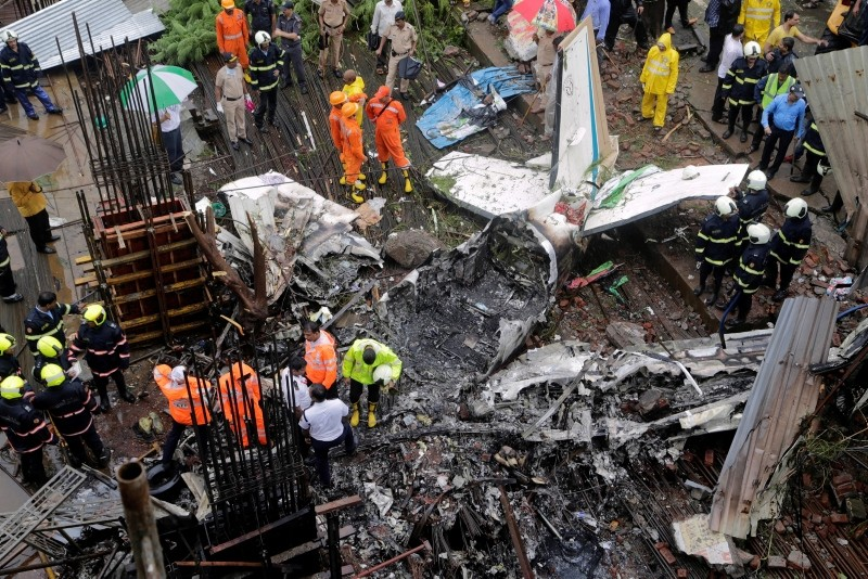 Rescuers stand amid the wreckage of a private chartered plane that crashed in Ghatkopar area, Mumbai, India, Thursday, June 28, 2018. (AP Photo)
