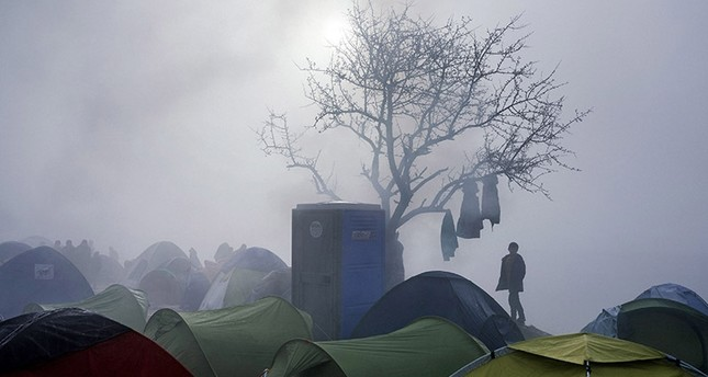 A boy stands among tents during a foggy morning at a makeshift camp near the Greek village of Idomeni on March 8, 2016. (AFP Photo)