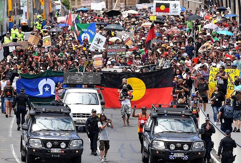 An Aboriginal protester holding a placard outside the Australian Prime Minister's Office (Reuters Photo)