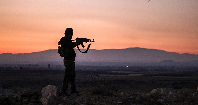 A Syrian opposition fighter aims his Kalashnikov assault rifle as he stands near the frontline against government forces west of the embattled southern city of Daraa on July 3, 2018. (AFP Photo)