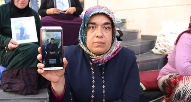 PKK terrorist Cafer Ceylan's mother Hatice Ceylan poses with his picture in front of the HDP HQ in Diyarbak?r during protests AA File Photo