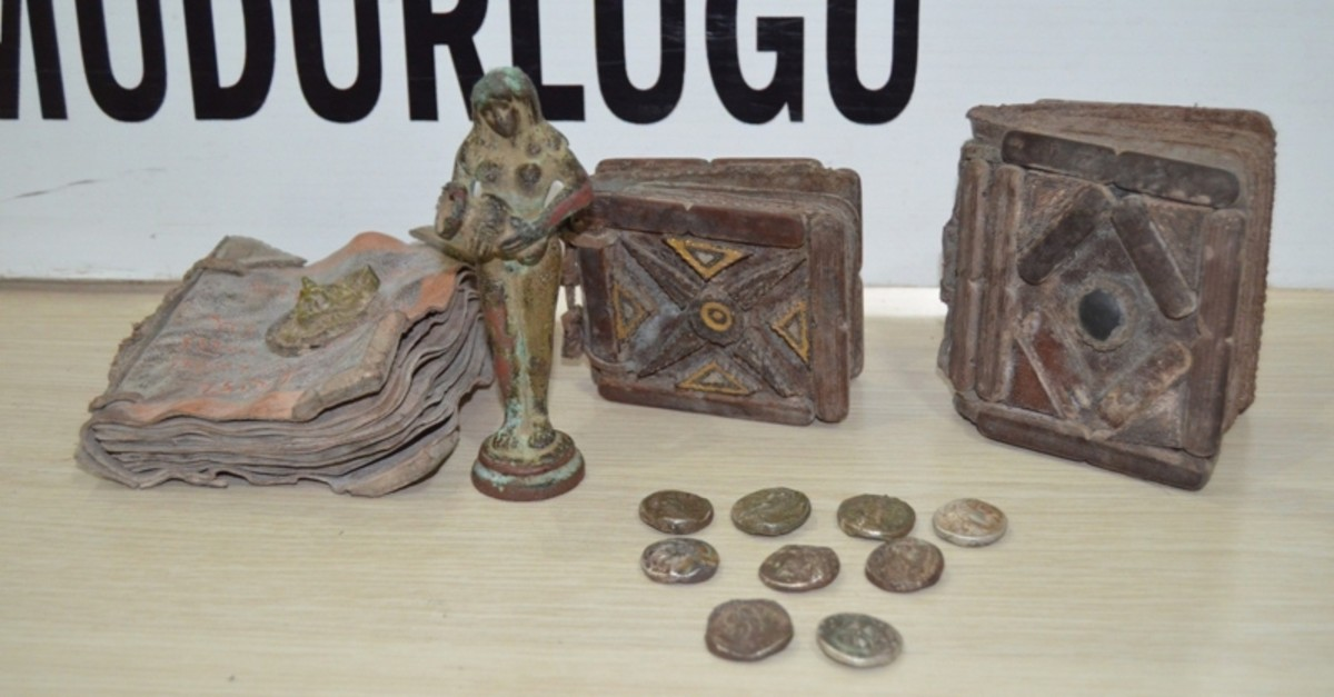 Photo dated Feb. 26, 2019 shows three Hebrew manuscripts, nine coins and a statue seized form smugglers in Osmaniye. (IHA Photo)