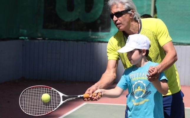 The Adana Tennis Federation's provincial representative Ferudun Açan trains Syrian children.