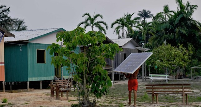 Solar panels donated by the World Wildlife Fund (WWF) and Brazilian government are carried to the village of Volta do Bucho in the Western Amazon region.