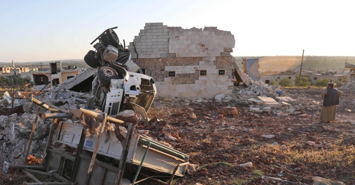 A man looks at rubble and damaged vehicles after reported airstrikes by the Syrian regime in the town of Kafranbel in Idlib province, June 28, 2019.