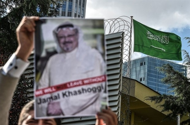 A protester holds a poster with a picture of Jamal Khashoggi outside Saudi Arabia's Consulate in Istanbul.