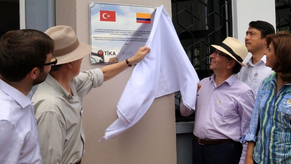Colombian President Santos, second from left, Turkish Ambassador Engin Yu00fcru00fcr, right, and Tu0130KA representative Mehmet u00d6zkan, left, unveil name plaque of the school.