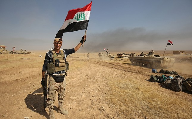 A member of the Iraqi forces poses for a photo holding his national flag as they advance towards the village of al-Ayadieh, north of Tal Afar, during the ongoing operation to retake the area from the Daesh group on Aug. 28, 2017. (AFP Photo)