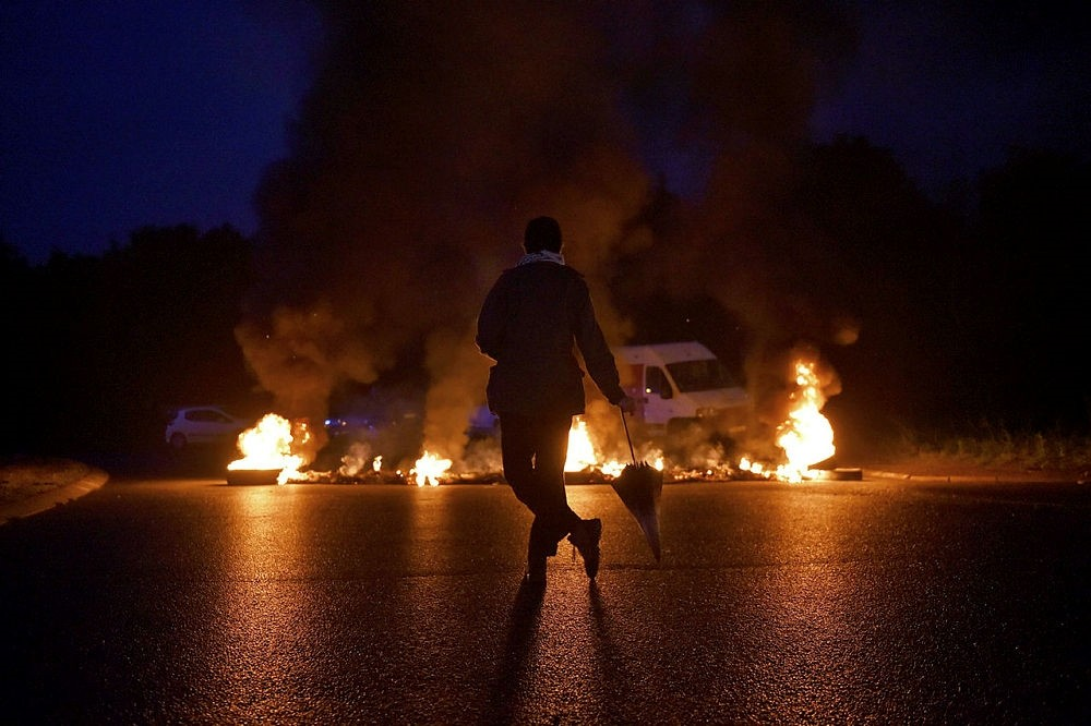 A protestor looks at a fire displayed on a traffic circle as union trade members block trucks on September 25, 2017 in Donges, western France. (AFP Photo)