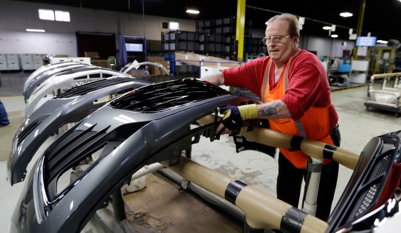 This Wednesday, Nov. 28, 2018, file photo shows Clifford Goff, a bezel assembler, transferring a front end of a General Motors Chevrolet Cruze during assembly at Jamestown Industries, in Youngstown, Ohio. (AP Photo)