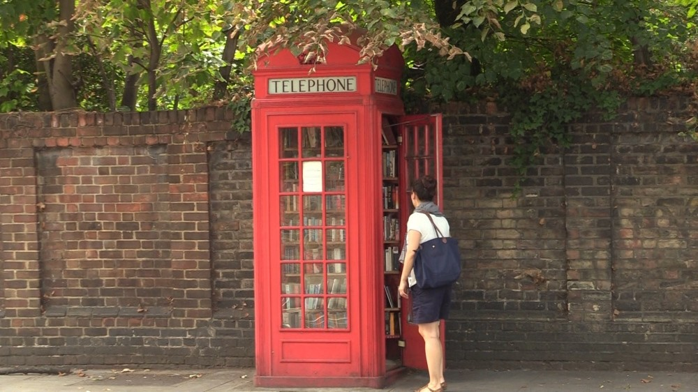 A woman stands near an iconic Red English Telephone booth used as a micro library in Lewisham district of London.