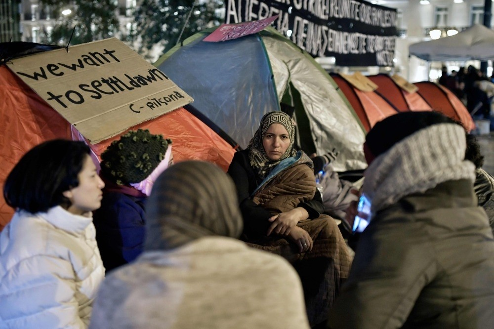 Refugees gather and sit by their tents at Athen's central Syntagma Square opposite Greek parliament, as refugee families protest against delays in reuniting with their relatives in other European countries, Nov. 1.