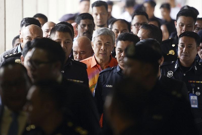 United Malays National Organization's (UMNO) President Ahmad Zahid Hamidi, center, walks out of court room at Kuala Lumpur High Court in Kuala Lumpur, Malaysia, Friday, Oct. 19, 2018. (AP Photo)