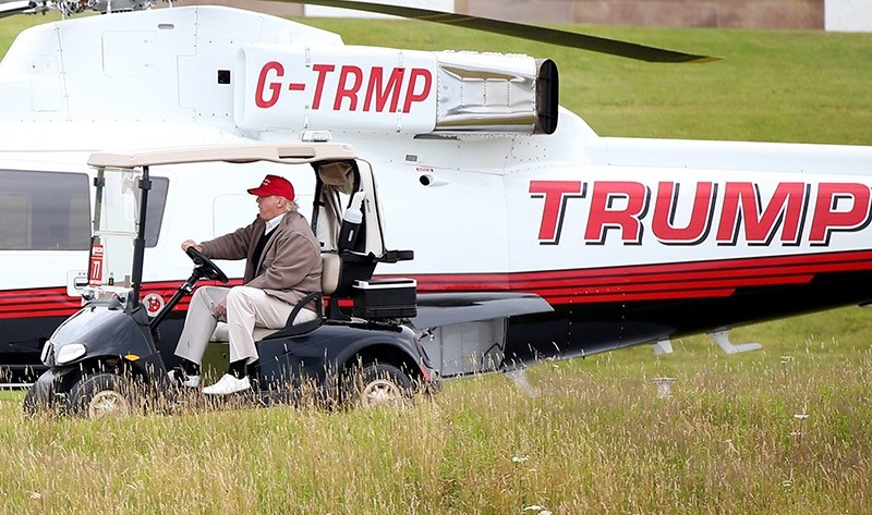 In this Friday, July 31, 2015 file photograph, U.S. President Donald Trump drives his golf buggy past his helicopter during the second day of the Women's British Open golf championship on his Turnberry golf course in Turnberry, Scotland. (AP Photo)