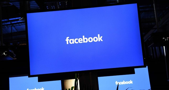 A Facebook logo is pictured on a screen ahead of a press conference to announce the launch of it's latest product Workplace, in central London on October 10, 2016. (AFP Photo)