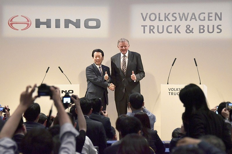 Andreas Renschler, right, a board member at Volkswagen AG and CEO of Volkswagen Truck & Bus, and Hino Motors President and Chief Executive Yoshio Shimo, left, pose for the media during a press conference in Tokyo, Thursday, April 12, 2018. (AP Photo)