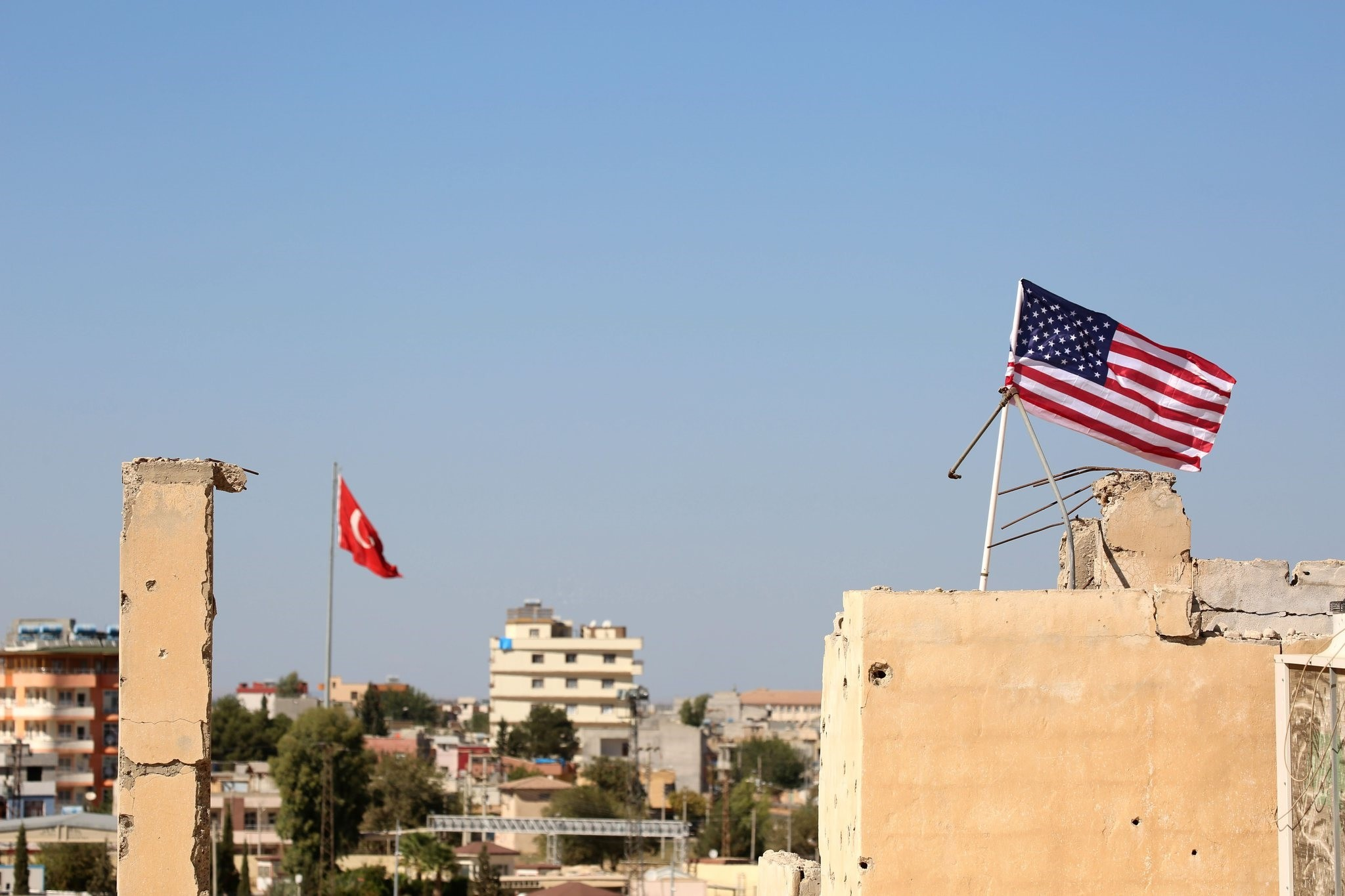 A U.S. flag fluttering above a building used by PYD forces in Tal Abyad, Syria on the border with Turkey, where a Turkish flag can be seen in the back, Sept. 17, 2016.