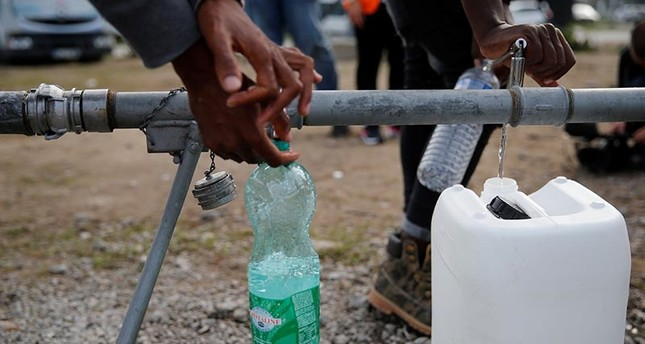Migrants fill bottles and jerrican at a portable drinking water system near the former jungle in Calais, France, August 23, 2017 (Reuters Photo)
