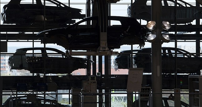 In this April 3, 2017 file photo E-Golf electric cars hang in the assembly line during the official production start in the German car manufacturer Volkswagen Transparent Factory (Glaeserne Manufaktur) in Dresden, eastern Germany. (AP Photo)